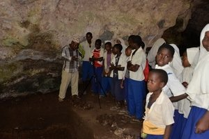 Salim Salim (Department of Archives, Museums, and Antiquities, Pemba) teaches a local school group about the prehistory of the cave