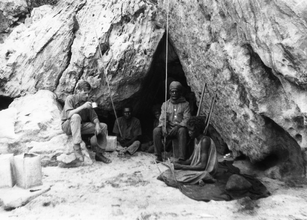 Rockshelter at Bathurst Head (Thartali) in eastern Cape York Peninsula, occupied by the expedition during field work. Pictured: Norman Tindale and local Aboriginal group. Photo by Herbert Hale. February 1927.