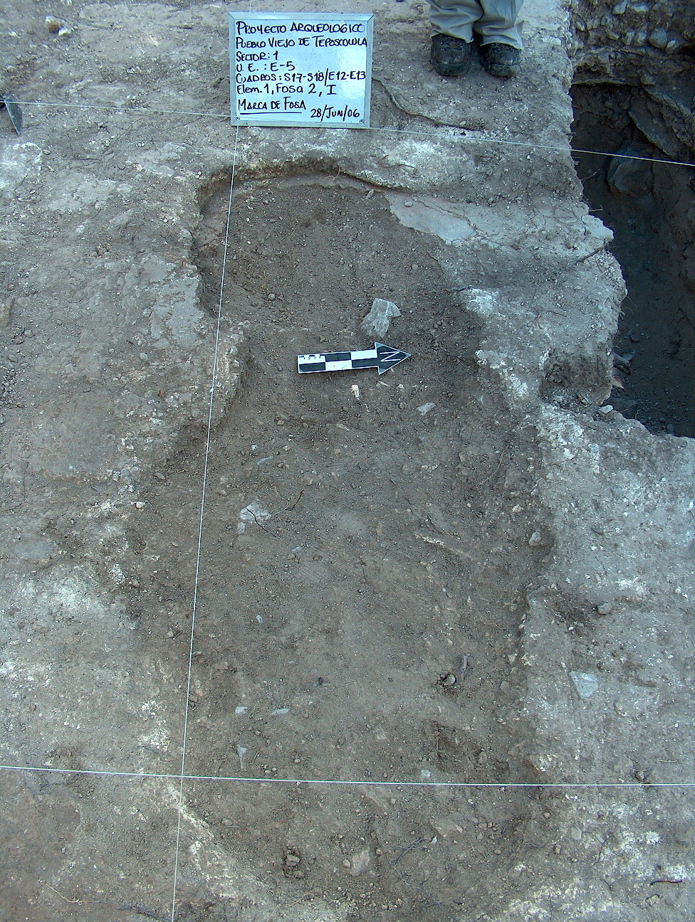 A mass burial in the Teposcolula-Yucundaa Grand Plaza, shown prior to excavation. It contained the remains of three individuals, all of whom tested positive for <em>S. enterica</em>. A second grave, visible at the top right, contained an additional two individuals who tested positive for <em>S. enterica</em>. Mass graves in the Grand Plaza were densely spaced and roughly cut into the plaster floor. The floor was never repaired, indicating the haste with which the site was abandoned shortly after the epidemic.