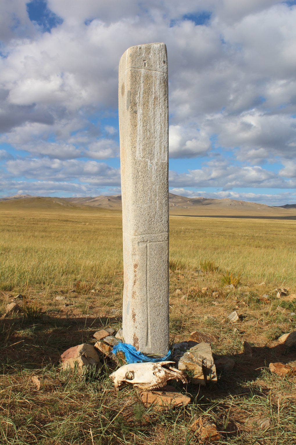A horse skull placed next to a deer stone in central Mongolia. Horse skulls are revered by modern herders, as are deer stones – this one has been decorated with a ceremonial blue prayer scarf.
